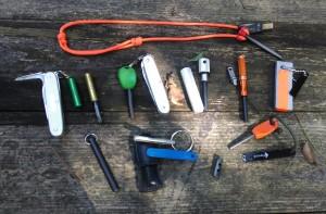 (Top) FireSteel.com, (left to right), SAK Bushcrafter with Wilderness Solutions Pendant in green aluminum and brass, SAK with Light My Fire, Aurora Fire Starter, Exacto Nanostriker, Doan's Mag Bar, (Bottom L to R) FireSteel.com, Sparky, FireSteel.com Toggle, LMF Scout.