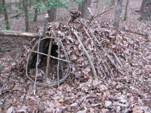 Front view of shelter  with door before being completely stuffed with leaf debris for insulation.