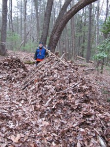 The author's son and a backside view of a debris shelter they constructed.