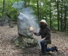 Steve Watts paying homage to Seton by blowing a bow drill coal to flame in front of Medicine Rock.